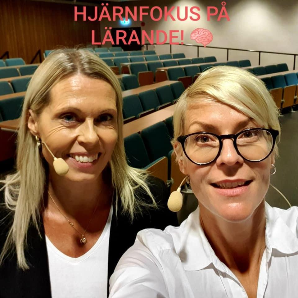 Lena och Annika framför massor av tomma stolar i en sal.